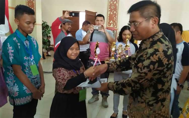Pelajar SMPN 1 Kuala Pembuang menerima piala juara 1 lomba musik tradisonal dan desain poster pada kegiatan FLS2N tingkat provinsi