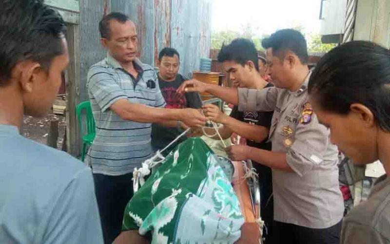 Polisi dan warga saat mengevakuasi korban bunuh diri.