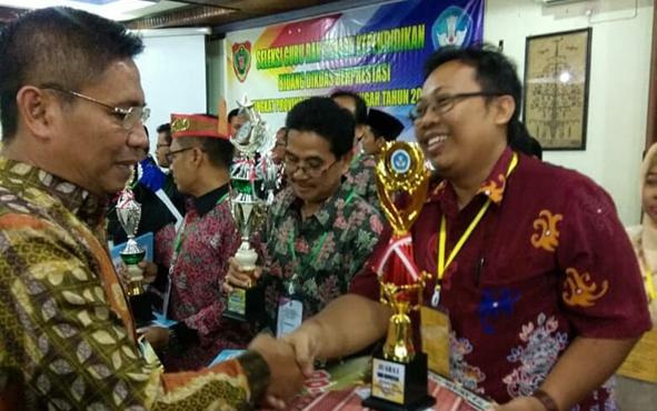 Guru sejarah SMAN 5 Palangka Raya, Endar Priyo Sulistiyo, berjabat tangan dengan Kepala Dinas Pendidikan Kalimantan Tengah Slamet Winarno.