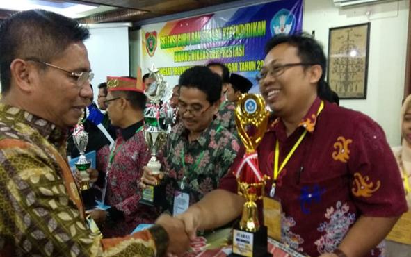 Guru sejarah di SMAN 5 Palangka Raya, Endar Priyo Sulistiyo, berjabat tangan dengan Kepala Dinas Pendidikan Provinsi Kalteng Slamet Winarno seusai menerima gelar juara pertama Guru Berprestasi tingkat Kalteng.