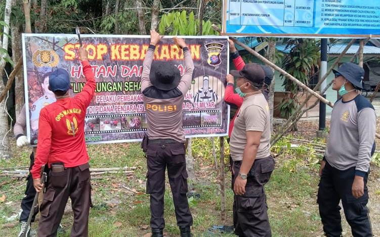 Anggota Polsek Dusun Selatan memasang spanduk larangan membakar hutan dan lahan.