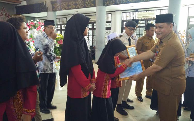 Sekretaris Daerah (Sekda) Kotim Halikinnor saat memberikan piagam penghargaan kepada sejumlah siswa di Kotim, pada kegiatan PGRI, Selasa, 23 Juli 2019.