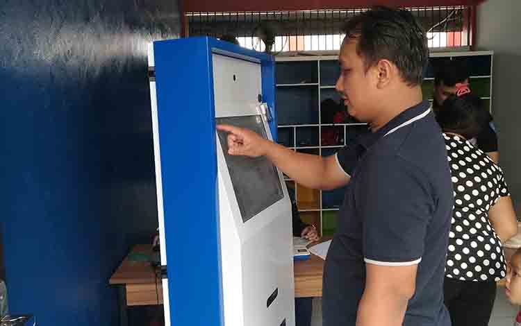 Petugas Rutan Kelas IIA Palangka Raya saat memeriksa komputer self service.