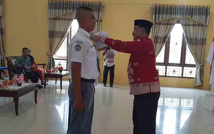 Kepala Disporapar Kabupaten Sukamara Ahmad Zubani saat memasang tanda pengenal calon Paskibra, Kamis, 1 Agustus 2019.