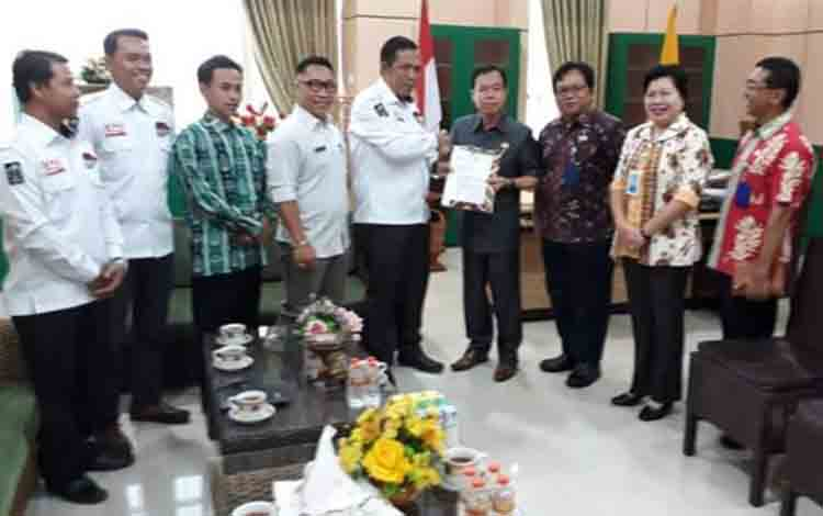 Ketua KPU Katingan Subandi menyerahkan dokumen 25 nama anggota DPRD terpilih kepada Bupati Katingan, Sakariyas untuk diteruskan ke Gubernur Kalteng, Kamis, 1 Agustus 2019.