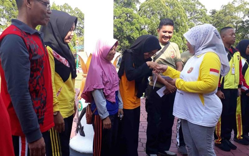 Bupati Kobar membagikan hadian voucher belanja ke peserta senam.