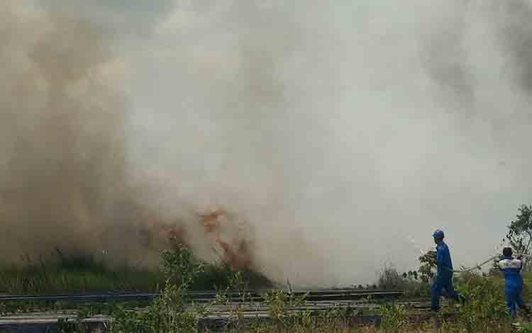 Sejumlah karyawan Stasiun Pengisian dan Pengangkutan Elpiji Khusus (SPPEK) saat berupaya melakukan pemadaman terhadap lahan yang yang terbakar, Senin, 5 Agustus 2019.