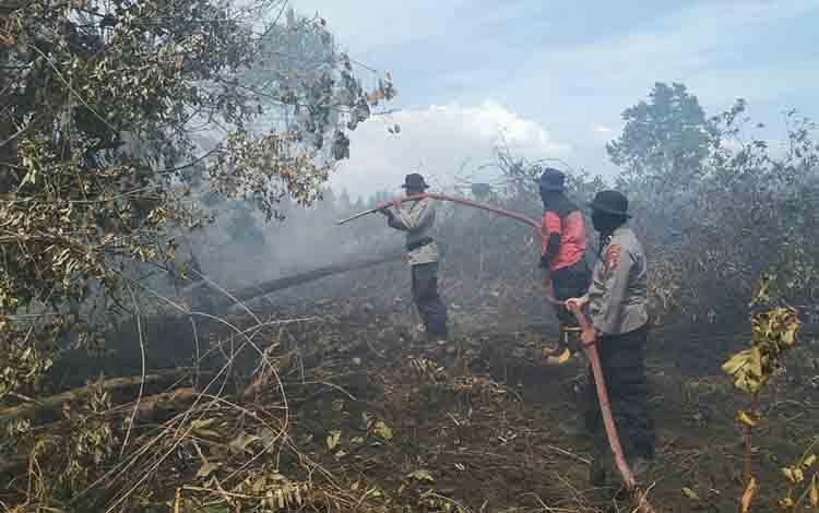 Petugas Polres Kotim saat berupaya melakukan pemadaman kebakaran lahan di Jalan HM Arsyad, Kecamatan Mentawa Baru Ketapang, Kotim, Senin, 5 Agustus 2019.