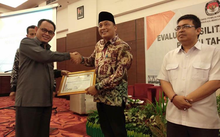 Ketua KPU Kalteng Harmain Ibrohim saat menyerahkan penghargaan kepada lembaga yang telah berkontribusi dalam pemilu, Rabu, 7 Agustus 2019.