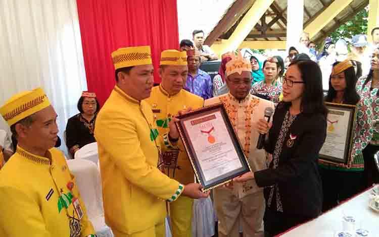 Bupati Hendra Lesmana menerima piagam penghargaan dari MURI untuk kategiri makan coto keladi korup matah