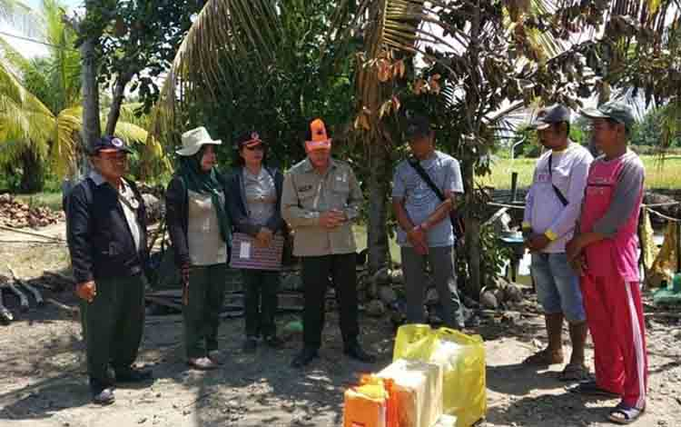 Personel BPBD Kabupaten Kapuas saat menyerahkan bantuan kepada korban musibah kebakaran di Desa Terusan Mulya, Kecamatan Bataguh