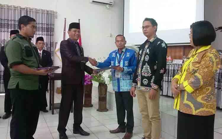 Ketua KPU Gunung Mas, Stepenson (kiri) menyerahkan berita acara dan surat keputusan kepada Ketua Bawaslu Gunung Mas, Walman Tristianto.