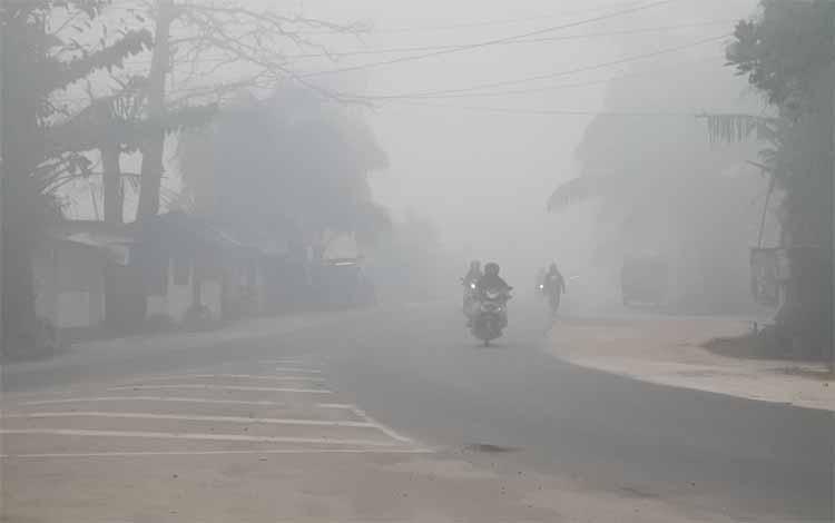 Sejumlah pengendara saat melintasi di tengah kabut asap yang terjadi di Sampit