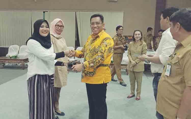 Modila Latifah Munawarah, angggota DPRD Kotim atau Ketua DPRD sementara saat menerima palu dari pimpimam sebelumnya dalam gladi paripurna istimewa.
