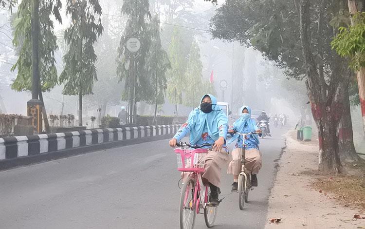 Sejumlah siswa saat berangkat sekolah ditengah kabut asap yang terjadi beberapa hari lalu.