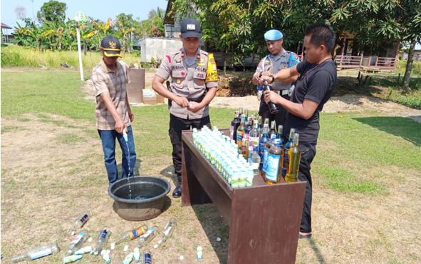Kapolsek Kapuas Murung Iptu Subandi didampingi anggotanya, dengan disaksikan tokoh masyarakatdan warga, memusnahkan miras ilegal, Selasa, 13 Agustus 2019.