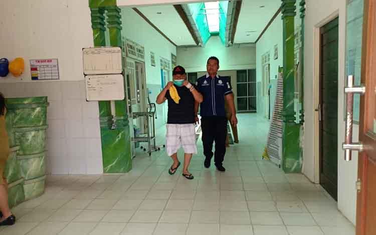 Salah satu tersangka dalam pengamanan petugas Polres Pulang Pisau saat pelimpahan ke kejaksaan, Selasa, 13 Agustus 2019.