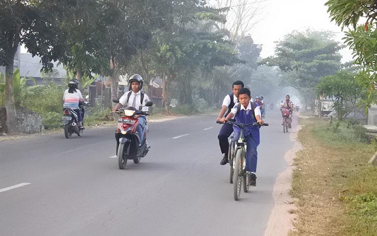 Sejumlah siswa saat hendak berangkat sekolah ditengah kabut asap tipis, beberapa waktu lalu.