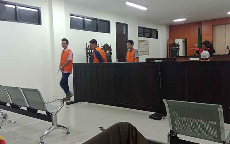 Tri Prasetyo, Aji Roy dan Harjo, terdakwa pencurian meninggalkan ruang sidang Pengadilan Negeri Sampit.