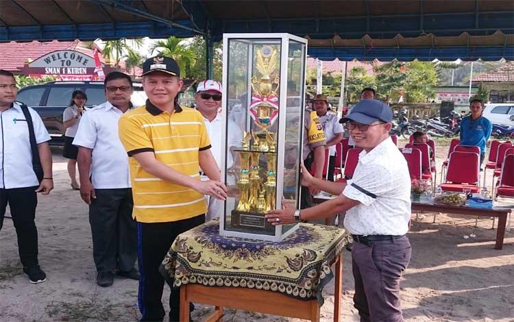 Bupati Gunung Mas, Jaya S Monong menyerahkan piala untuk diperebutkan, kepada Ketua Panitia Liga Desa Nusantara 2019, Subadio