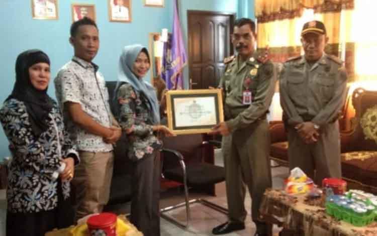 Ketua KPU Kapuas Jamilah Maisura menyerahkan piagam penghargaan kepada Kepala Satpol PP Kapuas pada Rabu, 14 Agustus 2019