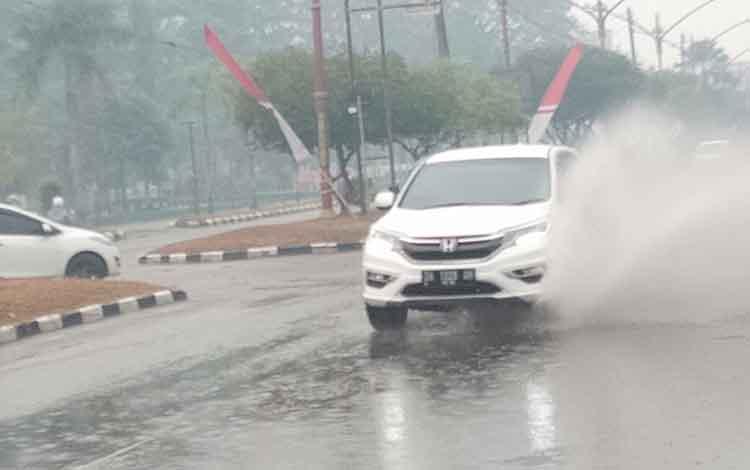 Sebuah mobil melintasi genangan air yang berada di Jalan Yos Sudarso, Rabu, 14 Agustus 2019.