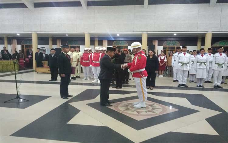 Bupati Barito Timur Ampera AY Mebas menyerahkan pedang pora kepada pasukan pengibar bendera