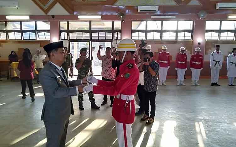 Bupati Barsel, Eddy Raya Samsuri menyerahkan pedang pora kepada salah satu anggota paskibra saat pengukuhan, Jumat, 16 Agustus 2019.