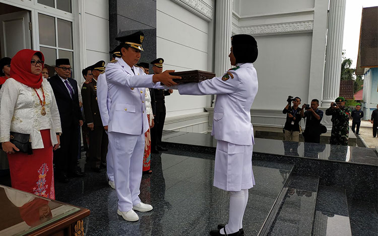 Bupati Barito Utara H Nadalsyah ketika menyerahkan bendera pusaka merah putih kepada Paskibraka.