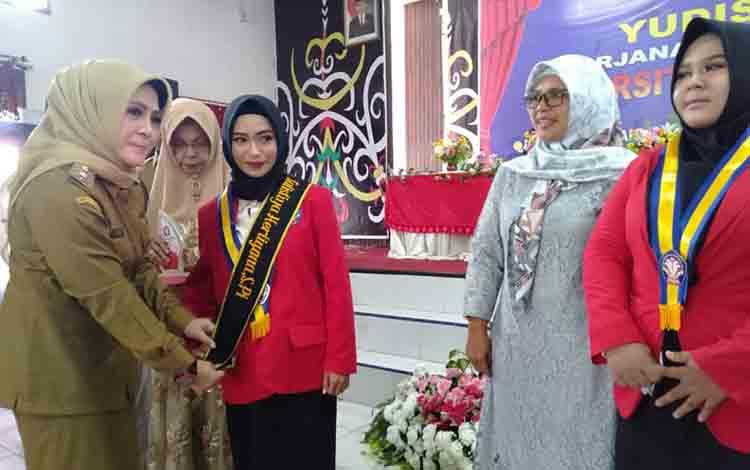 Wakil Bupati Seruyan Hj Iswanti ketika memberikan ucapan selamat kepada salah satu mahasiswa yang melaksanakan Yudisium Perguruan Tinggi di Kuala Pembuang, beberapa waktu lalu.