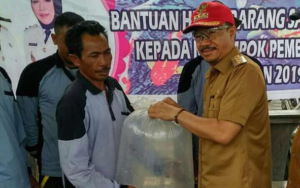 Bupati Seruyan Yulhaidir saat menyerahkan hibah bantuan bibit ikan nila kepada perwakilan kelompok pembudidaya ikan, di Dermaga Desa Pemantang Panjang, Selasa, 20 Agustus 2019 sore.
