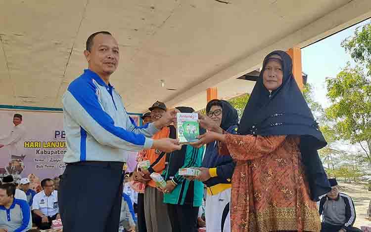 Bupati Sukamara, Windu Subagio saat menyerahkan bantuan susu kepada perwakilan lansia pada Halun ke 213 di Pantai Citra.