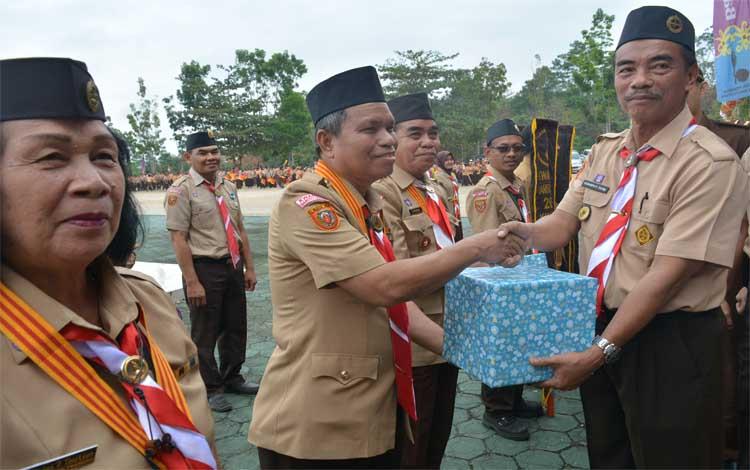 Wakil Bupati Barito Utara, Sugianto Panala Putra menyerahkan bingkisan kepada Ketua Kwarcab Pramuka Barito Utara, Asran