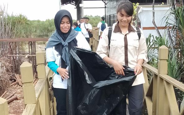 Dua remaja perempuan membawa plastik hitam untuk memungut sampah di kawasan Dermaga Kereng Bengkirai, Kota Palangka Raya, Rabu, 21 Agustus 2019.