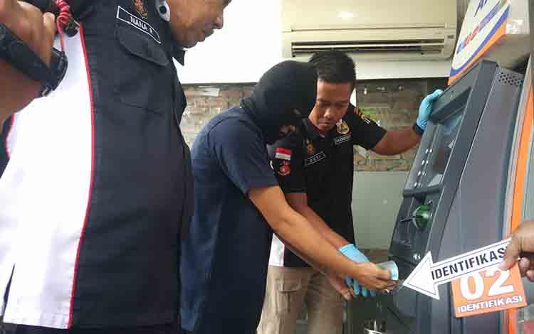Kasat Reskrim Polres Kotim AKP Achmat Budi Martono saat menyaksikan reka ulang pelaku pembobolan, di salah satu mesin ATM, Rabu, 21 Agustus 2019.