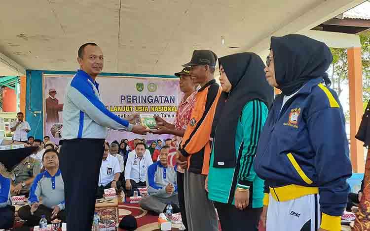 Bupati Sukamara Windu Subagio saat meganuerahkan bantuan susu kepada para lansia, Ranu, 21 Agustus 2019.