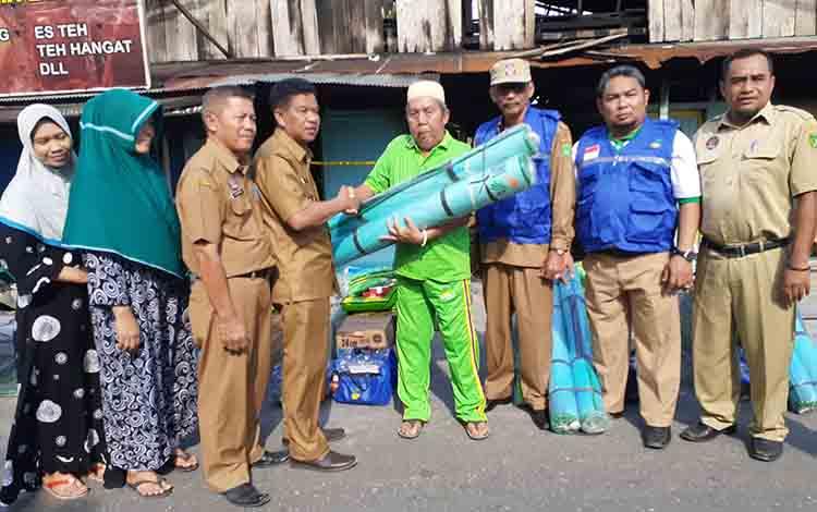 Wakil Bupati Sukamara H Ahmadi saat menyerahkan bantuan kepada salah satu korban kebakaran.