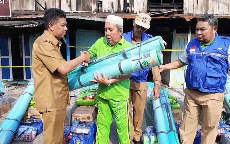 Wakil Bupati Sukamara, H Ahmadi saat menyerahkan bantuan kepada perwakilan korban kebakaran.