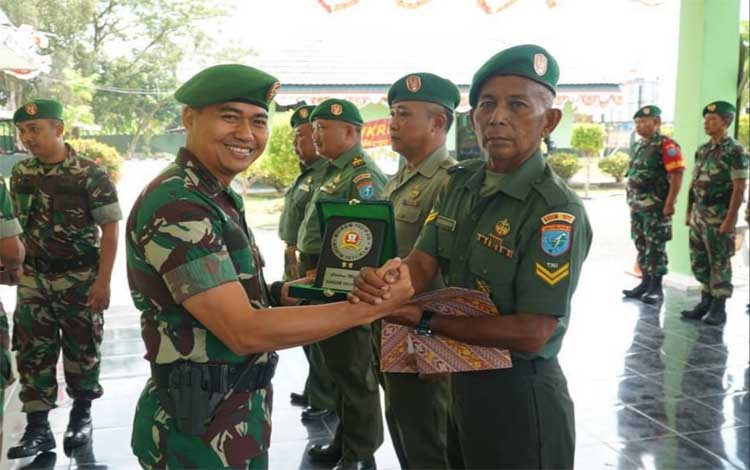 Dandim 1011 Kuala Kapuas Letkol Kav Bambang Kristianto Bawono menyerahkan cinderamata kepada personel yang purna tugas