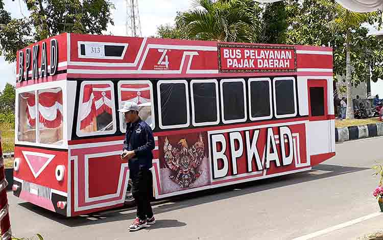 BPKAD Sukamara saat menampilkan miniatur bus pelayanan pajak daerah pada pawai pembangunan tahun 2019, Kamis, (22/8).