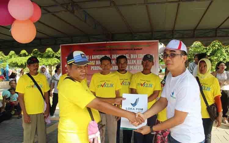 Kepala BPOM Kotawaringin Barat Kodon Tarigan berikan sertifikat lolos uji lab pada pedagang jajanan.