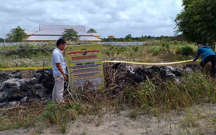 Anggota Polres Sukamara saat memasang garis polisi di lahan yang terbakar, Jumat, 23 Agustus 2019.
