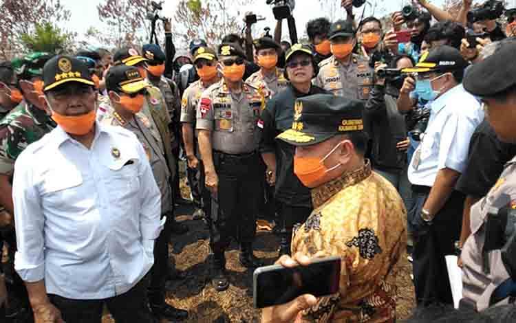 Gubernur Kalteng Sugianto Sabran (kanan), Menko Polhukam Wiranto (kiri) dan pejabat lainnya mengecek lahan yang terbakar di Jalan Soekarno, Jumat, 23 Agustus 2019.