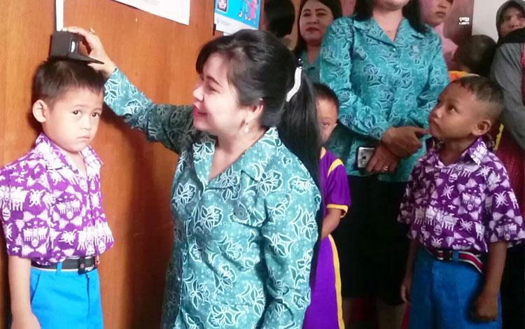 Ketua TP PKK Kabupaten Gunung Mas, Mimie Mariatie Jaya S Monong saat mengukur tinggi badan murid PAU