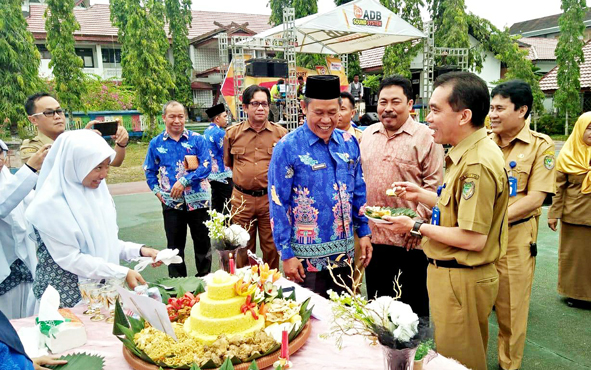 Plt Kepala Dinas Pendidikan Barito Utara Syahmiludin A Surapati memberikan nasi tumpeng kepada Kepala SMAN 1 Muara Teweh Razikinoor saat peringatab HUT sekolah, Senin, 26 Agustus 2019.