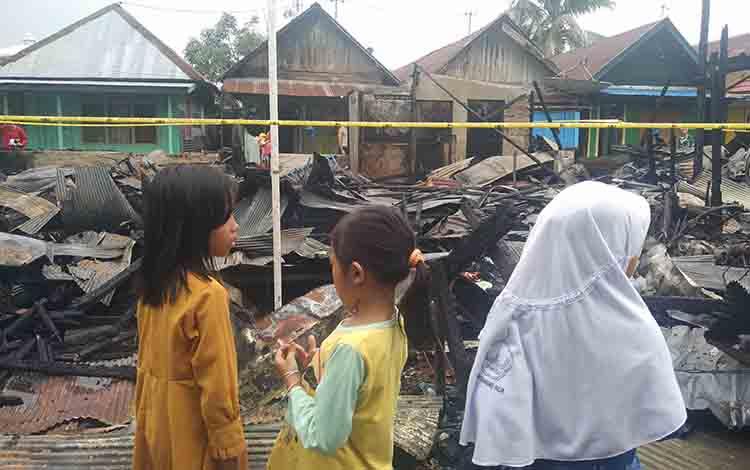 Tiga orang anak-anak saat melihat sisa-sisa puing kebakaran rumah yang terjadi di kompleks Pasar Keramat, Sampit, Selasa, 27 Agustus 2019