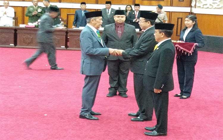 Reinhard Atu Narang menyerahkan palu pimpinan rapat kepada Duel Rawing, Rabu, 28 Agustus 2019