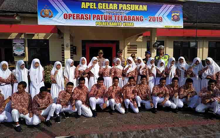 Kapolres Barito Utara AKBP Dostan Matheus Siregar beserta jajarannya berfoto bersama siswa seusai Apel Gelar Pasukan Operasi Patuh Telabang, Kamis, 29 Agustus 2019.