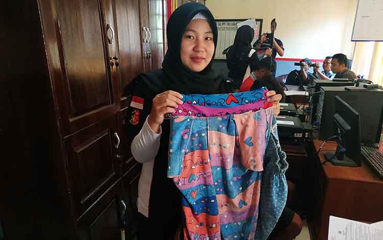 Anggota PPA Satreskrim Polres Barito Utara saat memperlihatkan barang bukti pakaian korban.