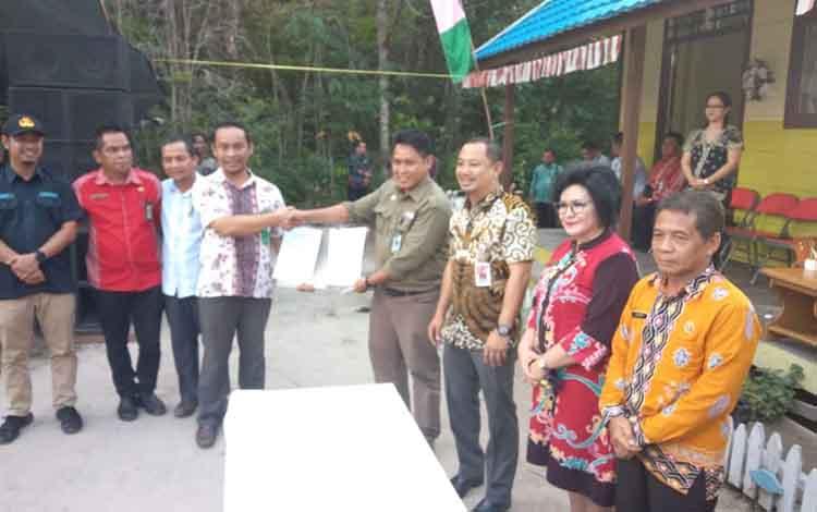 Pj Kades Madara, Kristy Briantomy (sebelah kiri) memegang perjanjian kerjasama pemanfaatan kawasan hutan.